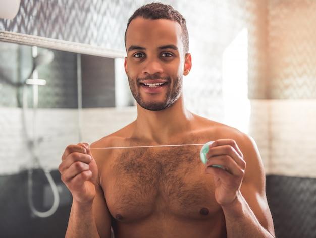 Hombre afroamericano guapo está sosteniendo un hilo dental.
