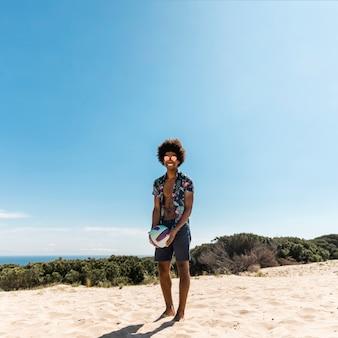 Hombre afroamericano hermoso que presenta con la bola en la playa