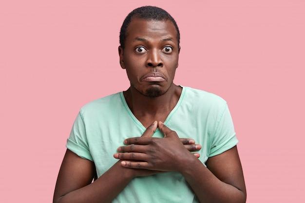 El hombre afroamericano indeciso de piel oscura desconcertado mantiene las manos en el pecho, mira con los ojos muy abiertos y se curva, expresa duda e incredulidad