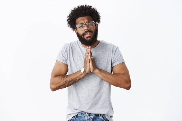 Hombre afroamericano inquieto necesitado con gafas y reloj tomados de la mano en oración haciendo muecas, pidiendo ayuda y favor pidiendo misericordia intensa y sincera, de pie molesto sobre la pared gris