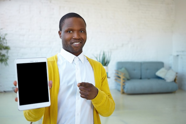 Hombre afroamericano joven atractivo alegre en ropa elegante que sostiene la pc del panel táctil digital, que sonríe ampliamente y que señala el dedo índice en la pantalla en blanco con espacio de copia para su texto y contenido publicitario