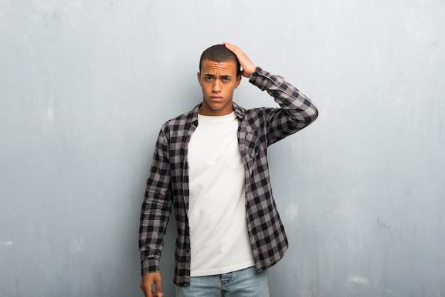 Hombre afroamericano joven con camisa a cuadros con una expresión de frustración