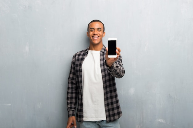 Hombre afroamericano joven con camisa a cuadros mirando a la cámara y sonriendo mientras usa el móvil