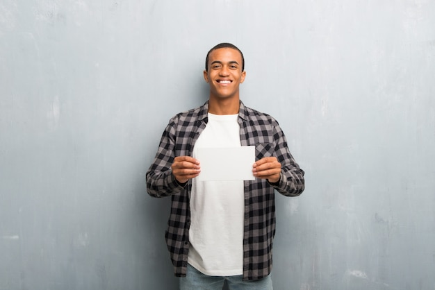 El hombre afroamericano joven con la camisa a cuadros que lleva a cabo un cartel blanco vacío para inserta un concepto