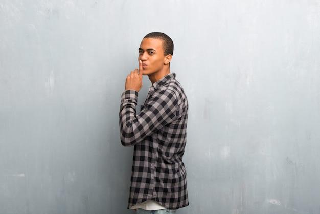 Hombre afroamericano joven con la camisa a cuadros que muestra una muestra del gesto cerrado de la boca y del silencio