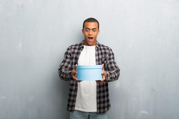 Hombre afroamericano joven con la camisa a cuadros que sostiene las cajas de regalo en manos