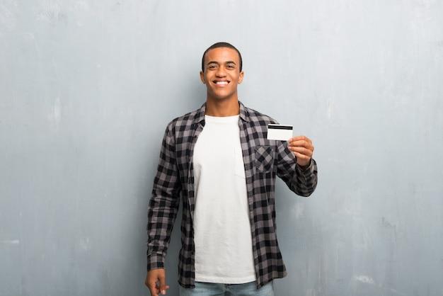 Hombre afroamericano joven con la camisa a cuadros que sostiene una tarjeta de crédito