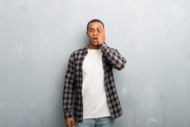 Hombre afroamericano joven con camisa a cuadros con sorpresa y expresión facial conmocionada