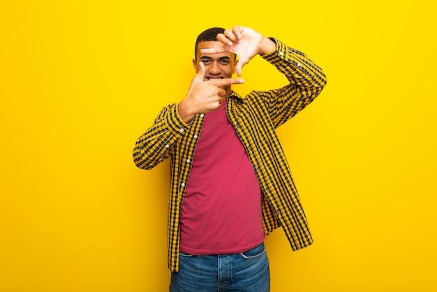 Hombre afroamericano joven en cara de concentración del fondo amarillo. símbolo de encuadre