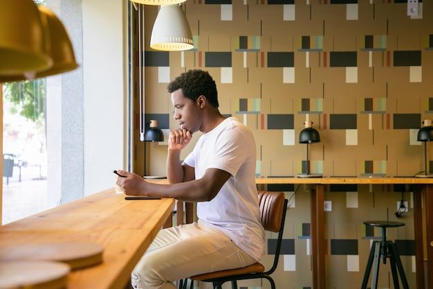 Hombre afroamericano joven centrado sentado en el escritorio en el espacio de trabajo conjunto o cafetería, con tableta