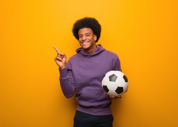Hombre afroamericano joven del deporte que sostiene un balón de fútbol que señala al lado con el finger