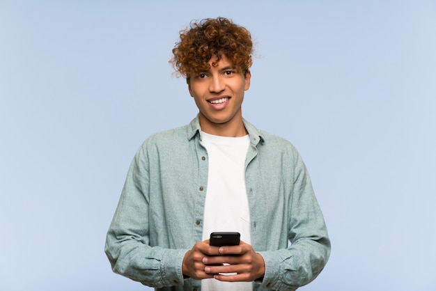 Hombre afroamericano joven sobre la pared azul aislada que envía un mensaje con el móvil