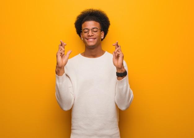 Hombre afroamericano joven sobre una pared naranja cruzando los dedos para tener suerte