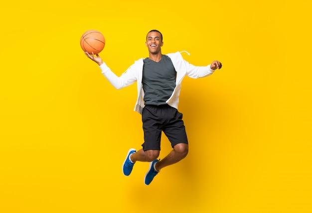 Hombre afroamericano jugador de baloncesto aislado en amarillo