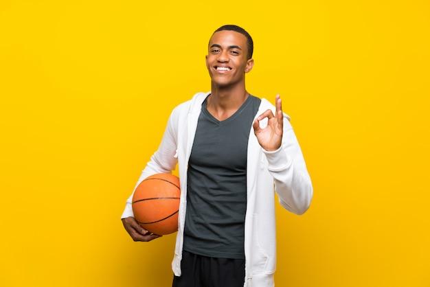 Hombre afroamericano del jugador de básquet que muestra la muestra aceptable con los dedos