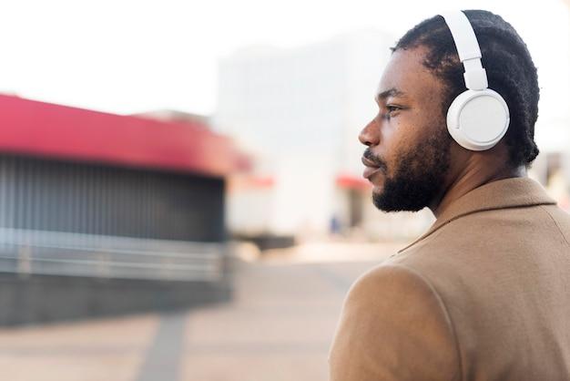 Hombre afroamericano de lado escuchando música a través de auriculares