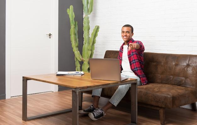 Hombre afroamericano con laptop en la sala de estar apunta con el dedo con una expresión de confianza