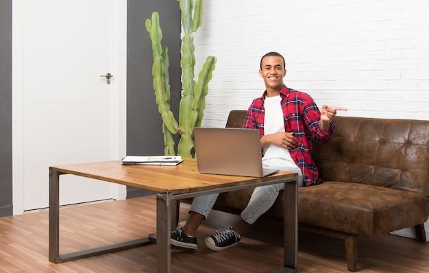 Hombre afroamericano con laptop en la sala de estar apuntando con el dedo hacia un lado en posición lateral