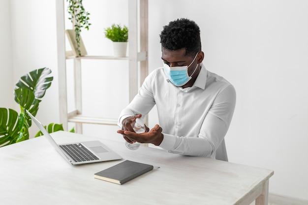 Hombre afroamericano con máscara y limpiando sus manos