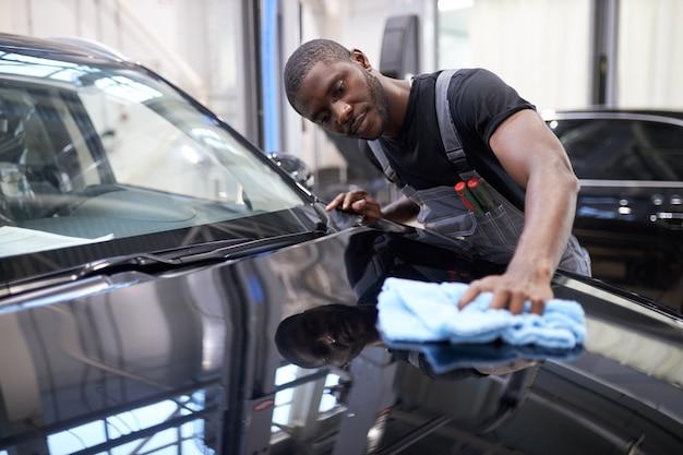Hombre afroamericano mecánico de automóviles limpia la superficie perfecta de la máquina después de pulir