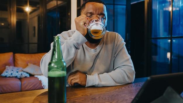 Hombre afroamericano de mediana edad bebiendo cerveza divirtiéndose feliz noche fiesta celebración en línea a través de videollamadas en la sala de estar en casa.