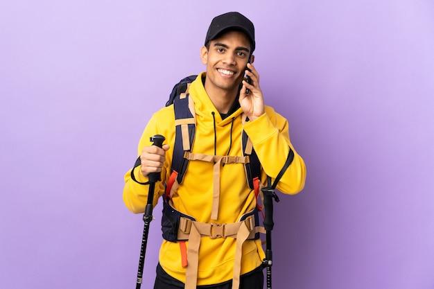 Hombre afroamericano con mochila y bastones de trekking manteniendo una conversación con el teléfono móvil con alguien