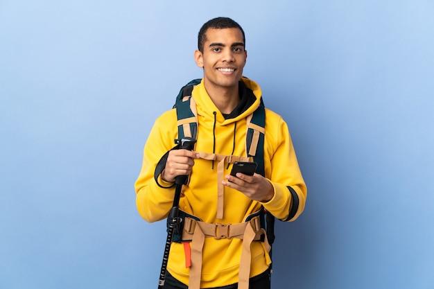 Hombre afroamericano con mochila y bastones de trekking sobre antecedentes aislados enviando un mensaje con el móvil