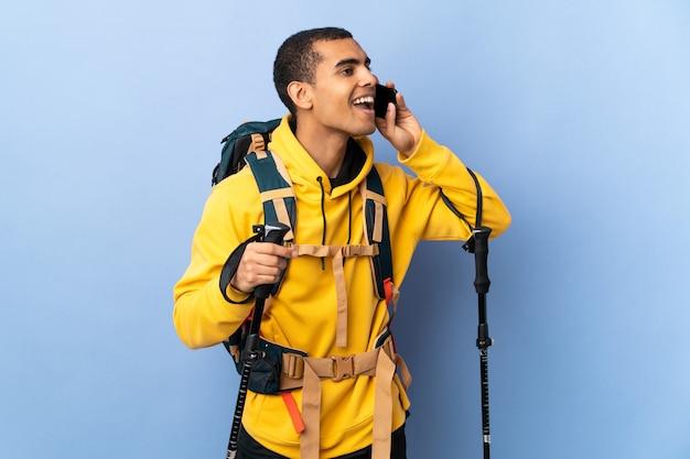 Hombre afroamericano con mochila y bastones de trekking sobre antecedentes aislados manteniendo una conversación con el teléfono móvil