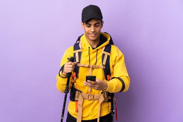 Hombre afroamericano con mochila y bastones de trekking sobre pared aislada enviando un mensaje con el móvil