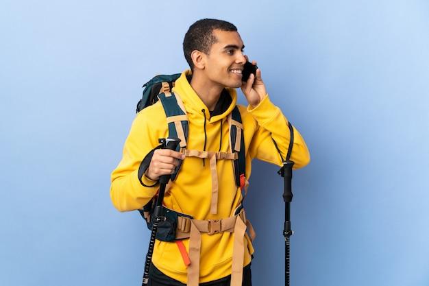 Hombre afroamericano con mochila y bastones de trekking sobre pared aislada manteniendo una conversación con el teléfono móvil con alguien