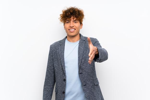 Hombre afroamericano de la moda que sacude las manos para cerrar un buen trato