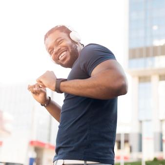 Hombre afroamericano moderno escuchando música a través de auriculares