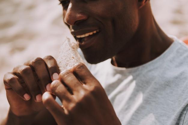 Hombre afroamericano mordedura sándwich al aire libre