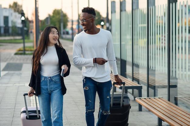 Hombre afroamericano y mujer asiática con pasaportes sostienen maletas y hablan en la parada de autobús.