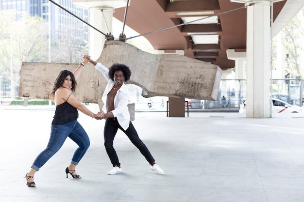 Hombre afroamericano y mujer caucásica practicando pasos de baile en una plaza de la ciudad