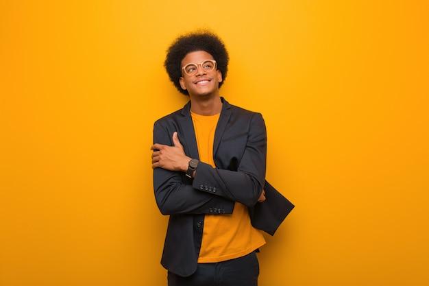 Hombre afroamericano del negocio joven sobre una pared anaranjada que sonríe confiado y que cruza los brazos, mirando para arriba