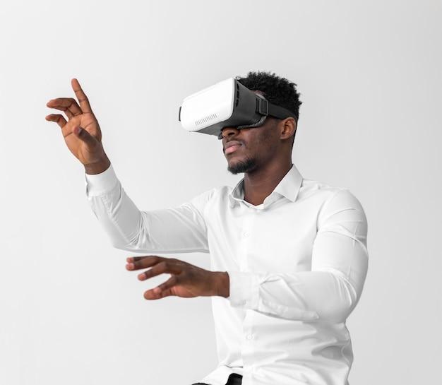 Hombre afroamericano de negocios con casco de realidad virtual