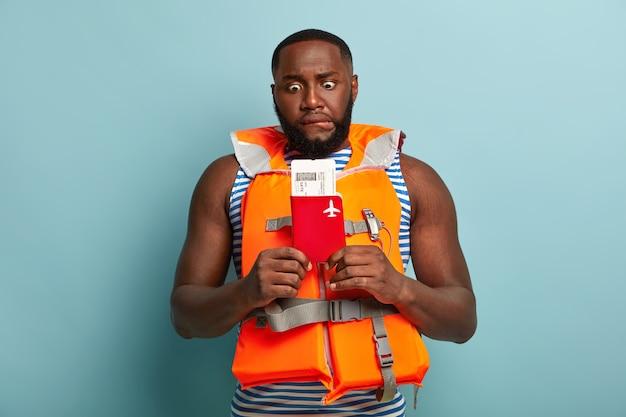 Hombre afroamericano nervioso se muerde los labios, sostiene el boleto de viaje y el pasaporte, se prepara para un viaje extremo, usa un chaleco salvavidas naranja