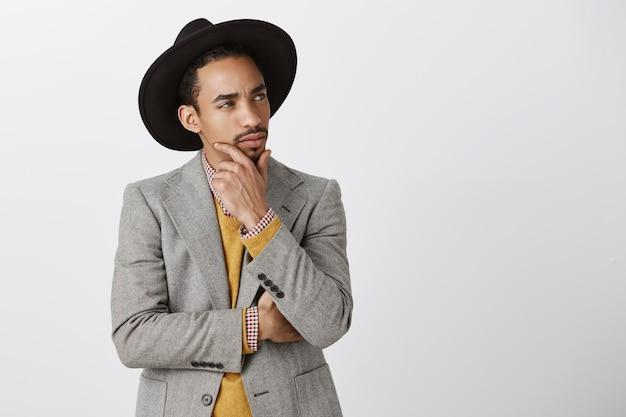 Hombre afroamericano pensativo en traje tomando una decisión, tocando la barbilla y mirando la esquina superior derecha, reflexionando sobre la elección