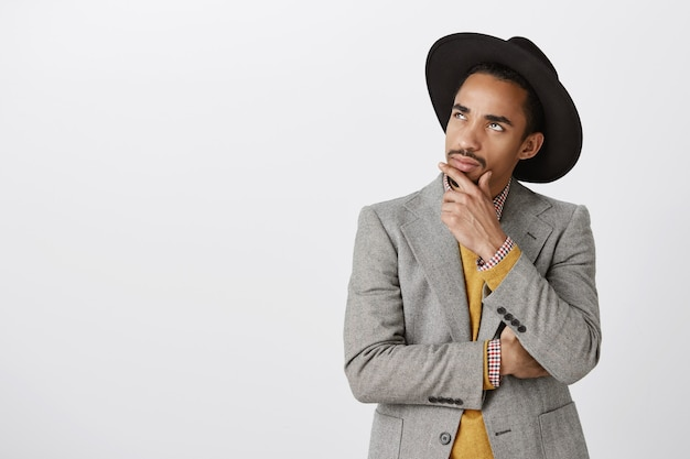 Hombre afroamericano pensativo en traje tomando una decisión, tocando la barbilla y mirando la esquina superior izquierda, reflexionando sobre la elección