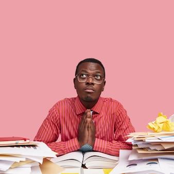 Hombre afroamericano de piel oscura ora por buena suerte, modelos sobre la pared rosada del estudio, mantiene las palmas juntas