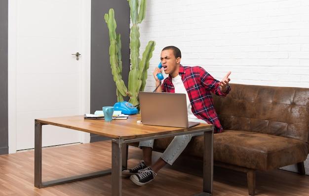 Hombre afroamericano con el portátil en la sala de estar hablando con un teléfono vintage