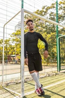 Hombre afroamericano posando con un balón de fútbol fuera
