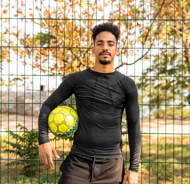 Hombre afroamericano posando con una pelota de fútbol al aire libre