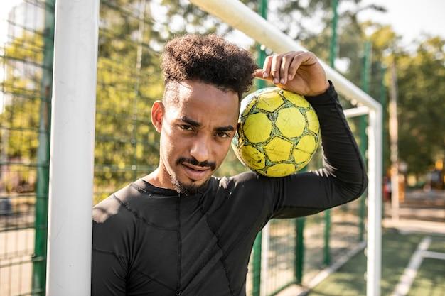 Hombre afroamericano posando con una pelota de fútbol en un campo