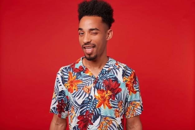 El hombre afroamericano positivo joven viste en camisa hawaiana, mira a la cámara y guiña un ojo, está parado sobre fondo rojo.