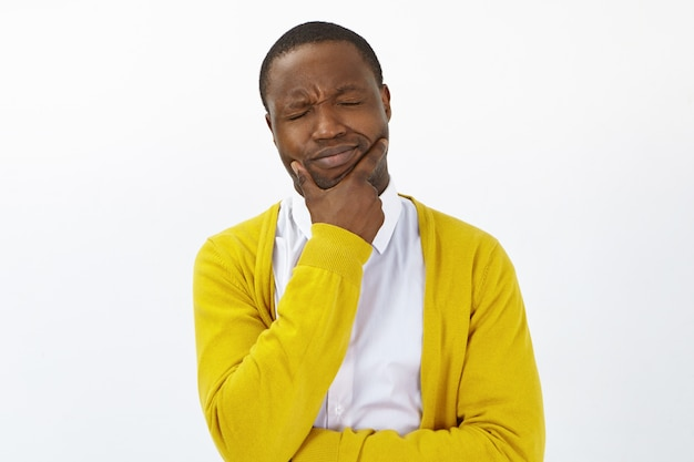 Hombre afroamericano preocupado joven frustrado que lleva a cabo la mano en la barbilla que experimenta dolor de muelas terrible, cierra los ojos, tiene mirada del sufrimiento doloroso. personas, estilo de vida, salud, enfermedad y dolor