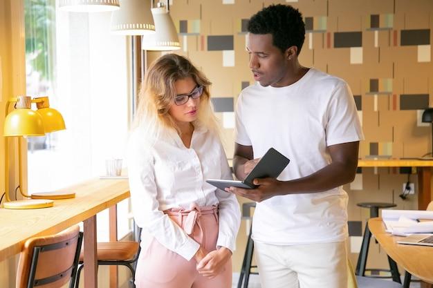 Hombre afroamericano que muestra la pantalla de la tableta al cliente rubio