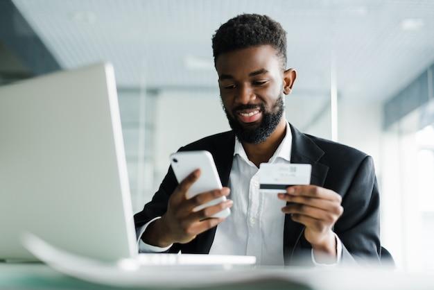 Hombre afroamericano que paga con tarjeta de crédito en línea mientras realiza pedidos a través de internet móvil haciendo transacciones utilizando la aplicación de banco móvil.