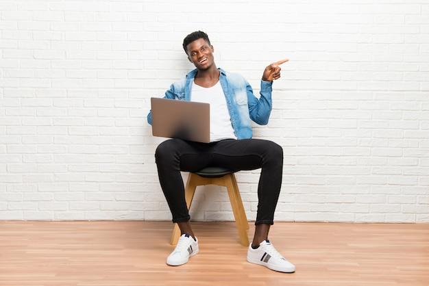 Hombre afroamericano que trabaja con su computadora portátil apuntando el dedo hacia un lado y presentando un producto
